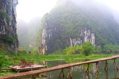 Bamboo terrace chairs jetty mystic mountains, Vietnam. Bamboo patio with chairs and a pier at the lake with view at misty karst mountains just before sunrise stock photo
