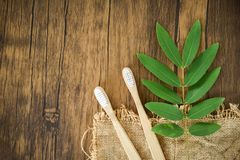 Bamboo toothbrush and green leaf on rustic background - Zero waste Bathroom use less plastic concept. Bamboo toothbrush and green leaf on rustic background / royalty free stock photo
