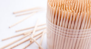 Bamboo toothpicks. Round bamboo toothpicks in plastic container, white background stock images