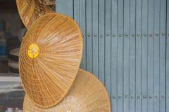 Bamboo weave hat hanging on metal door. Close up bamboo weave hat hanging on metal door Royalty Free Stock Image