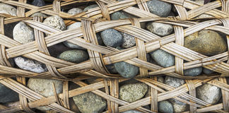 Bamboo weaved container full of pebbles called Longshi Royalty Free Stock Images