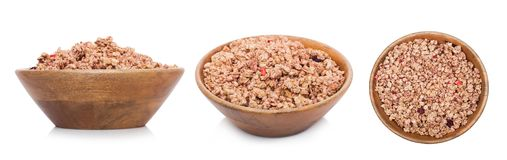 Bamboo wood bowl with organic granola cereal. Bamboo wood bowl with natural organic granola cereal summer fruits flakes on white.Top view stock images