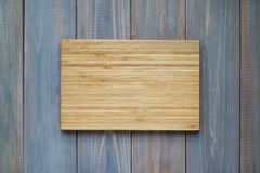 Bamboo wood cutting board on a wooden gray background.  royalty free stock image