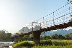 Bambubro över Nam Song River på den Vang Vieng byn royaltyfria bilder