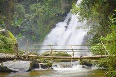 Bambubro över vattenfallet Arkivfoton