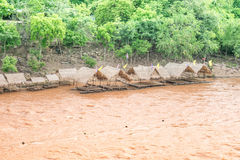 Bambuflotte på Muddy vatten som flödar i floden Royaltyfria Bilder