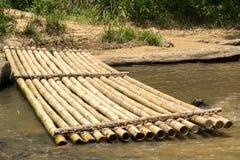 Bambuflotten och sliten timmer loggar in en flodbank Royaltyfri Fotografi