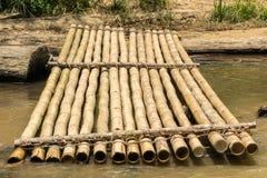 Bambuflotten och sliten timmer loggar in en flodbank Royaltyfri Foto