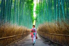 BambuForest Asian kvinna som bär den japanska traditionella kimonot på bambuskogen i Kyoto, Japan royaltyfri foto