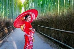 BambuForest Asian kvinna som bär den japanska traditionella kimonot på bambuskogen i Kyoto, Japan arkivfoto
