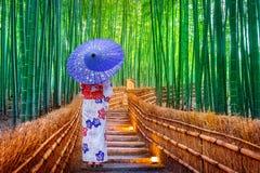 BambuForest Asian kvinna som bär den japanska traditionella kimonot på bambuskogen i Kyoto, Japan arkivfoton