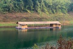 Bambuhusbåten svävar på behållaren Arkivfoto