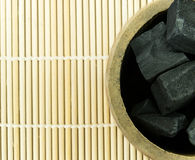 Bambukol i bamburör på matt bambu fotografering för bildbyråer