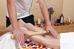 Bambumassage - Wellnesmassage - på en blondin Royaltyfria Bilder