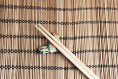 Bambupinnar på en handgjord origamipinnehållare Arkivfoton
