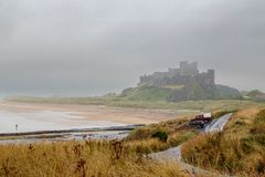 Bamburgh城堡&雨步行者 免版税库存照片