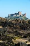 Bamburgh Castle. Viewed across rockpools Stock Image