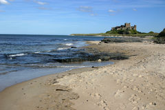Bamburgh Castle. On the north east coast of the UK in northumberland at high tide on a bright day Stock Images