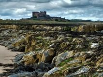Bamburgh castle, Northumberland, in profile against a brooding sky royalty free stock image