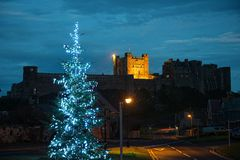 Bamburgh Castle, Northumberland, from the West. Bamburgh Castle, Northumberland, England, UK, from the West, at dusk, with a Christmas tree in the foreground Royalty Free Stock Photos