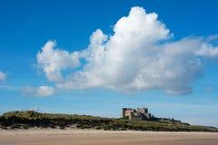 Bamburgh kasztel od odległości Anglia z jasnym niebieskim niebem i jaskrawymi chmurami Fotografia Stock