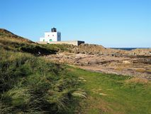 Bamburgh Lighthouse on the Northumberland coast, England. Bamburgh Lighthouse against a blue sky on the coast of Northumberland, England royalty free stock photography