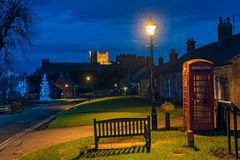 Bamburgh, Northumberland, England, UK, at dusk. Bamburgh village, Northumberland, England, UK, at dusk, with Bamburgh Castle in the background, at Christmas Stock Photos