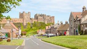 Bamburgh by och slott Arkivfoto