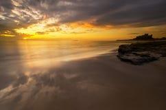 Bamburgh strandsoluppgång Arkivfoto