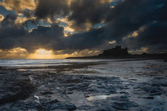 Bamburgh Sunrise. A view from the beach of Banburgh Castle which has been silhouetted against the morning sun Stock Photography
