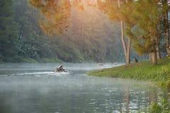 Bambus, der durch den Nebel auf dem See am Morgen flößt Stockfotos