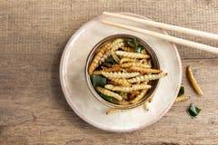 Bambus- essbare Wurminsekten knusperig oder Bambus-Caterpillar in einer keramischen Schüssel auf einer hölzernen Tabelle Das Konz lizenzfreies stockfoto