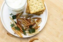 Bambus- essbare Wurminsekten knusperig oder Bambus-Caterpillar mit Pl?tzchen im keramischen Teller Das Konzept von Proteinnahrung stockfoto