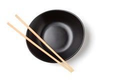 Bambusessstäbchen und schwarze Schüssel Stockbild