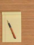 Bambuskrivbord, gult block, penna, kopieringsutrymme Arkivfoton