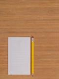Bambuskrivbord med den vita notepaden Royaltyfria Bilder