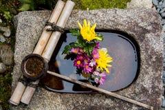 Bambusleven på en stenhandfat fyllde med en blommaordning i Kyoto Japan Arkivbild