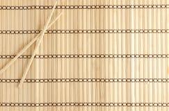 Bambusmatte für Sushi mit hölzernen Essstäbchen Lizenzfreie Stockfotografie