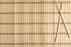 Bambusmatte für Sushi mit hölzernen Essstäbchen Stockfotos