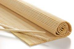 Bambusmatte für Sushi mit hölzernen Essstäbchen Lizenzfreie Stockbilder