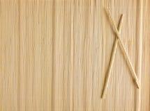 Bambusmatte für Sushi mit hölzernen Essstäbchen Stockfoto