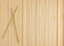 Bambusmatte für Sushi mit hölzernen Essstäbchen Stockbild