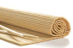 Bambusmatte für Sushi mit hölzernen Essstäbchen Stockbilder