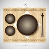 Bambusmatte mit den Platten und Essstäbchen, die für das Mittagessen einstellen Stockbilder