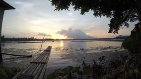 Bambusowa tratwa unosi się na zanieczyszczającym jeziorze przy zmierzchem zbiory