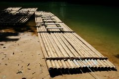 Bambusowa tratwa unosi się nad jasną rzeką w lesie Zdjęcia Royalty Free
