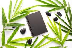 Bambusowy liścia zen tło Czarny papierowy notatnika mockup Zielony bambusowy liść i plażowy otoczaka mieszkanie nieatutowi Zdjęcia Royalty Free