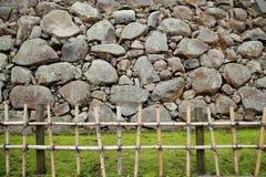 Bambusowy słupa fench, trawy murawa i nieregularna kształtna kamienna ściana, Fotografia Stock