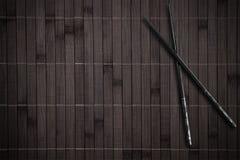 Bambusplacemat mit Steuerknüppeln lizenzfreie stockbilder