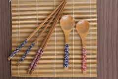 Bambussushiwerkzeuge über einer Bambusmatte Stockfotos